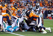 Carolina Panthers middle linebacker Luke Kuechly (59) tries in vain to stop Denver Broncos running back C.J. Anderson (22) as he runs the ball with an assist block from Denver Broncos offensive tackle Russell Okung (73) on a fourth down play good for a first and goal at the one yard line in the fourth quarter during the 2016 NFL week 1 regular season football game against the Carolina Panthers on Thursday, Sept. 8, 2016 in Denver. The Broncos won the game 21-20. (©Paul Anthony Spinelli)