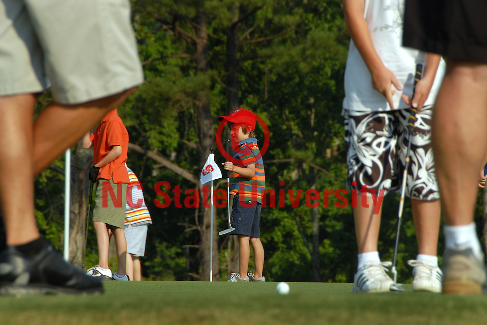 Golf campers putt around before class begins. PHOTO BY ROGER WINSTEAD