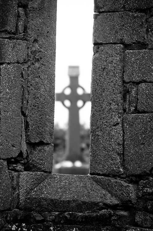 One of the crosses in the graveyard is framed through a window.