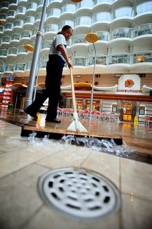 A crew member tries to dry op the deck after a heavy rain storm on the first day of cruise onboard the cruise ship Oasis of the Seas. The ship, currently the largest in the world, is owned by Royal Carribean Cruise Line.