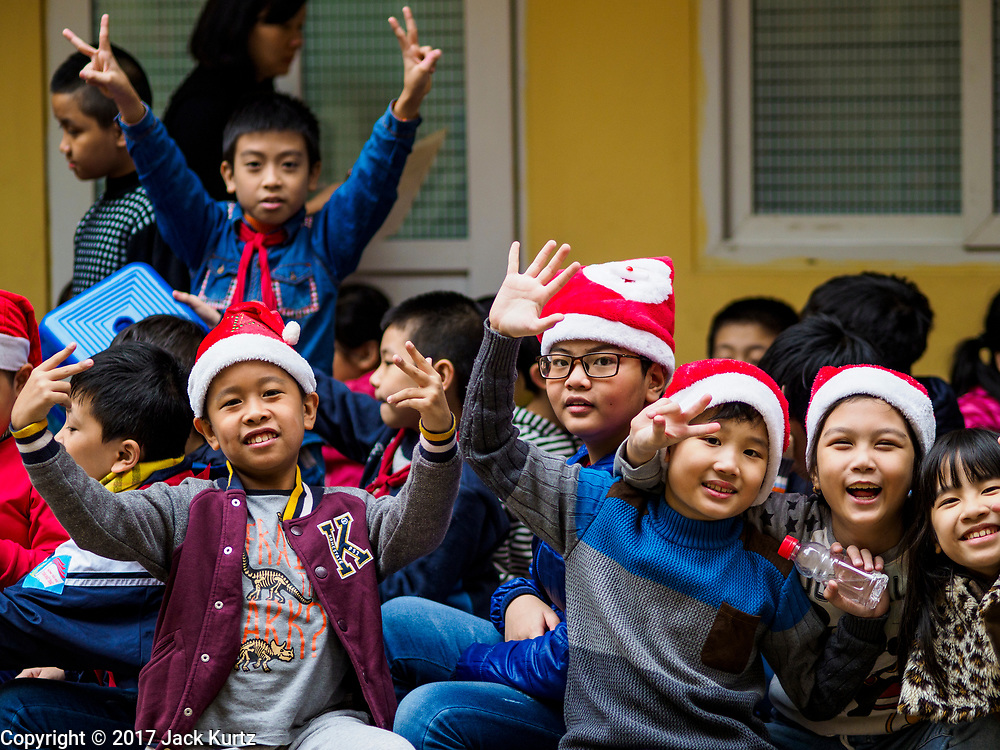 """22 DECEMBER 2017 - HANOI, VIETNAM:  Children at a school Christmas party in the old quarter of Hanoi. The old quarter is the heart of Hanoi, with narrow streets and lots of small shops but it's being """"gentrified"""" because of tourism and some of the shops are being turned into hotels and cafes for tourists and wealthy Vietnamese.   PHOTO BY JACK KURTZ"""