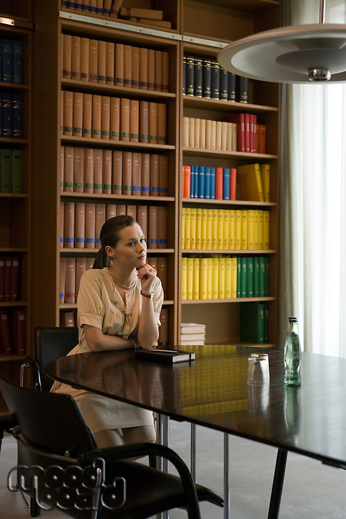 Pensive young woman at table in library