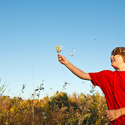 A nine year old boy plays with milkweed pods in a field at Elmwood Farm in Hopkinton, Massachusetts. Fall.