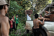 Workers from the relocation site arrive in the village of Kbal Romeas to collect teak wood from abandoned houses. Having no choice but to move away or drown, 89 out of 139 familes from Kbal Romeas agreed to be relocated in a scorching dusty piece of land along the main road to Ratanakiri. The villagers were offered two options: either accept $6000 per family and re-build a house by themselves or move into a small concrete house with a tin roof with 5 hectares of land to farm. Like many other promises though, no official document has been yet provided.