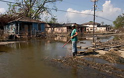 30 Sept, 2005. New Orleans, Louisiana. Lower 9th ward.  Hurricane Katrina aftermath. <br /> The remnants of the lives of ordinary folks, now covered in mud as the flood waters remain. A lady from the Humane Society sets off into the water in search of animals to rescue.<br /> Photo; ©Charlie Varley/varleypix.com