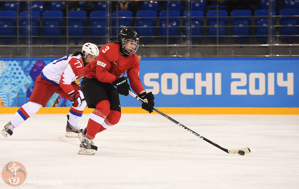 Feb 15, 2014; Sochi, RUSSIA; Switzerland defenseman Sarah Forster (3) skates with the puck as Russia defenseman Inna Dyubanok (77) gives chase in a women's quarterfinals ice hockey game during the Sochi 2014 Olympic Winter Games at Shayba Arena.