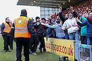 Lincoln City fans gesture the Brighton fans and invade the pitch and stewards tackle during the The FA Cup fourth round match between Lincoln City and Brighton and Hove Albion at Sincil Bank, Lincoln, United Kingdom on 28 January 2017. Photo by Phil Duncan.