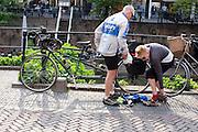 Twee vakantiefietsers op een tandem zijn bezig met hun bagage.<br /> <br /> Two cyclists with a tandem bike are on holiday  in  downtown Utrecht.
