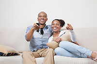 Portrait of young African American couple watching TV at home