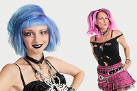Portrait of happy young and senior female punks against gray background