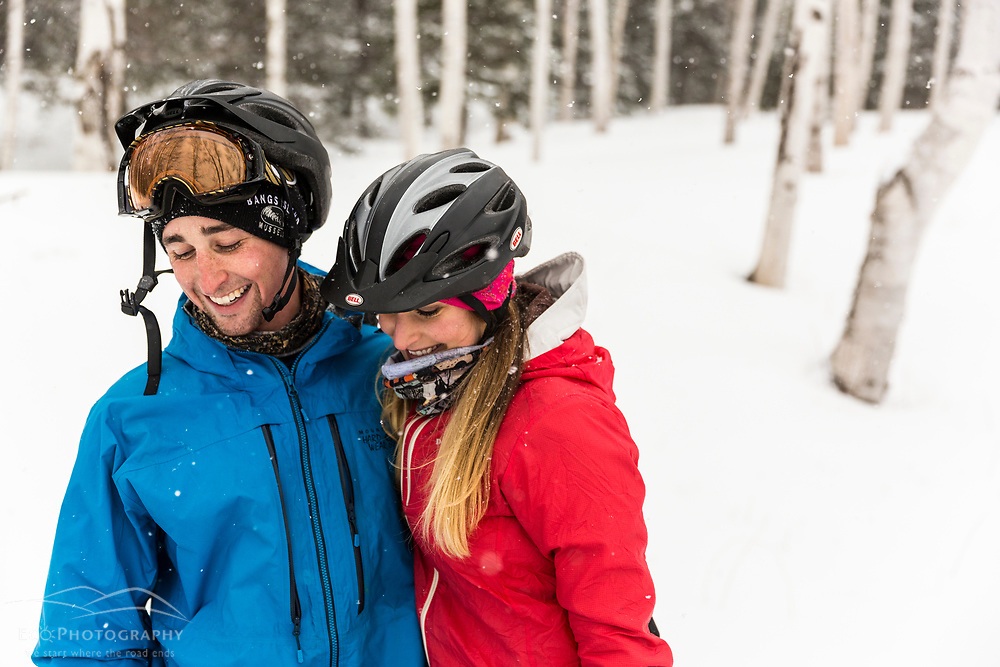 A couple takes a break from fat tire biking on a snowy winter day in New Hampshire's White Mountains.