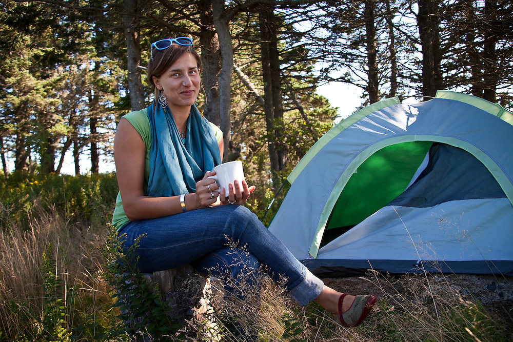 Woman sititing on tree stump drinking coffee in from of her camping tent