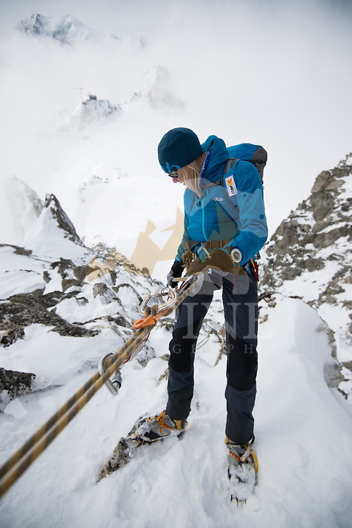 Squash Falconer, a female British adventurer, as seen preparing for a quick rappel off the snowy ridge of Aiguilles Marbrées on a cloudy winter day in Mont Blanc Massif.