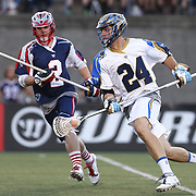 Ryan Flanagan #24 of the Charlotte Hounds keeps the ball from Scott Ratliff #2 of the Boston Cannons during the game at Harvard Stadium on May 17, 2014 in Boston, Massachuttes. (Photo by Elan Kawesch)