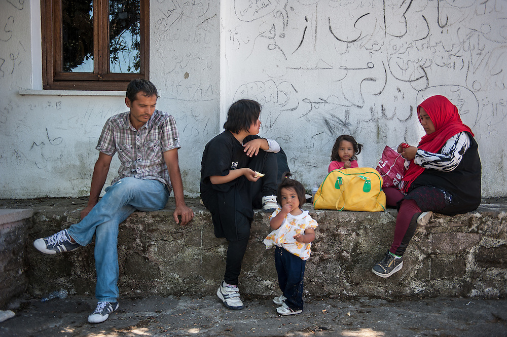 Alizada Amir from Kabul area, Afghanistan and his family rest in the shadow of a church yard near the village of Mantamados. Refugees land at the northern shores of the island of Lesbos and then they have to walk the 9 hour distance to one of the camps.