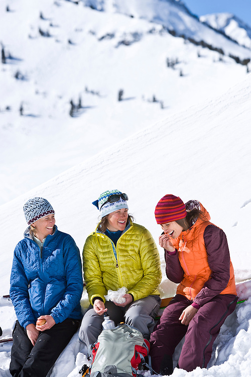 Three women friends share lunch and laughter while ski touring in the Wasatch Mountain backcountry near Alta, Utah.