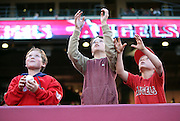 ANAHEIM, CA - APRIL 15:  Fans reach for a ball during the Los Angeles Angels of Anaheim game against the Oakland Athletics at Angel Stadium on Tuesday, April 15, 2014 in Anaheim, California. The Athletics won the game 10-9 in eleven innings. (Photo by Paul Spinelli/MLB Photos via Getty Images)