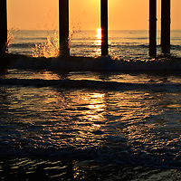 The base of the St. Johns County Ocean Pier silhoutted at sunrise with waves crashing against it, St. Augustine Beach, Florida
