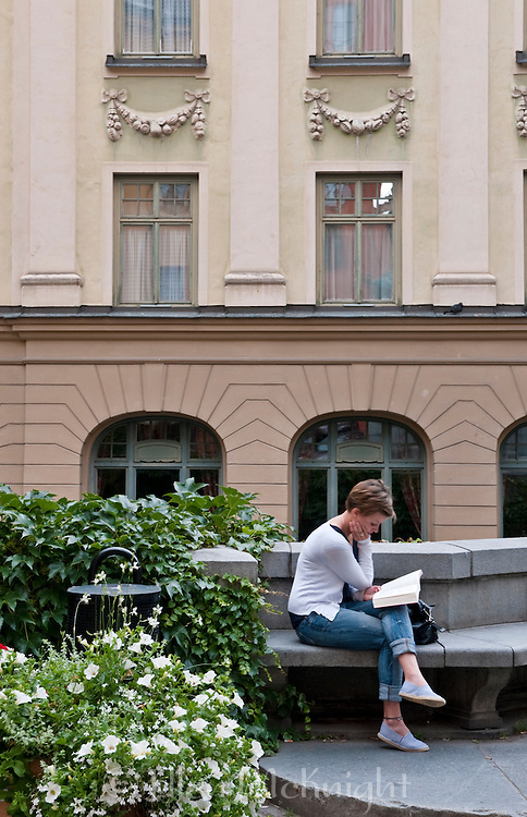 Woman reading in Gamla Stan (Old Town), Stockholm, Sweden