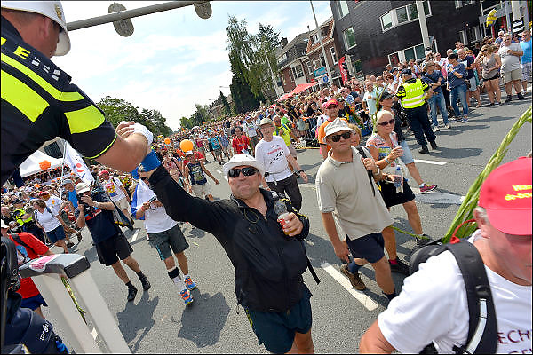 Nederland, Nijmegen, 24-7-2015Het vierdaagselegioen loopt over de Via Gladiola Nijmegen binnen. Op een van de kruispunten waar het verkeer doorgelaten wordt regelt een politieman met een helm van de Engelse Bobby het verkeer en maakt er zijn eigen show van.  Na een feestelijke intocht volgt de uiteindelijke finish en het ophalen van het kruisje, vierdaagsekruisje, op de Wedren. Iedere deelnemer krijgt een bloem, gladiool, uitgerijkt. The International Four Day Marches Nijmegen is the largest marching event in the world. It is organized every year in Nijmegen mid-July as a means of promoting sport and exercise. Participants walk 30, 40 or 50 kilometers daily, and on completion, receive a royally approved medal, Vierdaagsekruis.The participants are mostly civilians, but there are also a few thousand military participants. In 2004 a restriction on the maximum number of registrations is set to 45,000. More than a hundred countries have been represented in the Marches over the years.Foto: Flip Franssen/Hollandse Hoogte