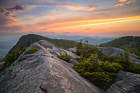 The bright red orb of the sun sets over the western mountains of Maine as seen from Tumbledown Mountain near Weld.