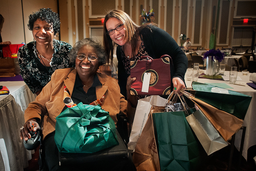 """Ebony Porter (left) and Emily Stern (right) help Carolyn Lewis (center) claim her prizes after the """"Power of the Purse"""" silent auction at the Women in Philanthropy conference on Thursday, March 14th in Baker Ballroom. Lewis placed bids on several items and ended up having the winning bid on six purses. Photo by: Ross Brinkerhoff."""