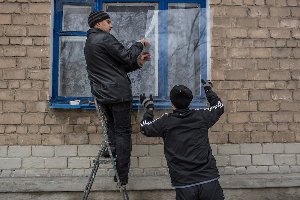 DONETSK, UKRAINE - JANUARY 23, 2015: Men weather seal a window at School 337, which was struck and damaged two days earlier by a rocket attack in Donetsk, Ukraine. Schools in Donetsk have been closed this week due to increased fighting, and will remain closed indefinitely. After the rebels finally took control of the heavily contested airport in Donetsk from the Ukrainian Army, they have promised an offensive to extend their territory further. CREDIT: Brendan Hoffman for The New York Times