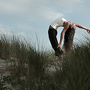 Tara Folton performs yoga on the beach.