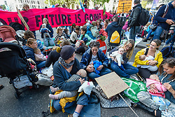 © Licensed to London News Pictures. 09/10/2019. LONDON, UK.  Mothers and their babies take part in The Mothers' March during day 3 of Extinction Rebellion's climate change protest in the capital.  Activists marched from Westminster Abbey to Whitehall to stage a sit-down demonstration against the effects of climate change and the future for their children.  Photo credit: Stephen Chung/LNP