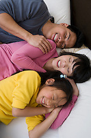 Mother, father and daughter lying down on bed with eyes closed