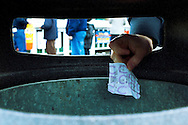 Male hand placing losing betting slip into bin. Focus on hand and slip.