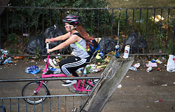 © Licensed to London News Pictures. 27/08/2019. London, UK. A woman cycles past rubbish left along a canal tow path in Notting Hill, west London, in the aftermath of the 2019 Notting Hill carnival. The two day event is the second largest street festival in the world after the Rio Carnival in Brazil, attracting over 1 million people to the streets of West London. Photo credit: Ben Cawthra/LNP