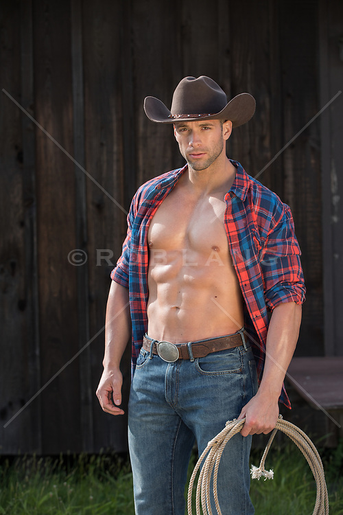 hot rugged muscular cowboy with an open shirt by a barn