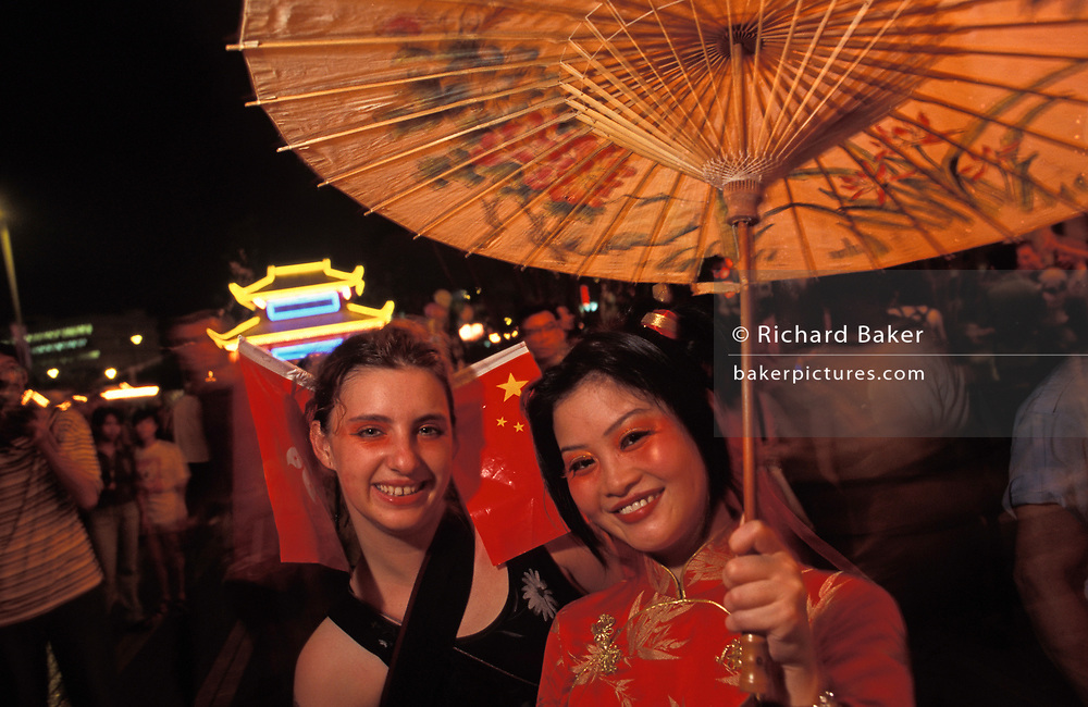Two Chinese and European women smile during a handover party on the eve of the handover of sovereignty from Britain to China, on 30th June 1997, in Hong Kong, China. Midnight signified the end of British rule, and the transfer of legal and financial authority back to China. Hong Kong was once known as 'fragrant harbour' (or Heung Keung) because of the smell of transported sandal wood.