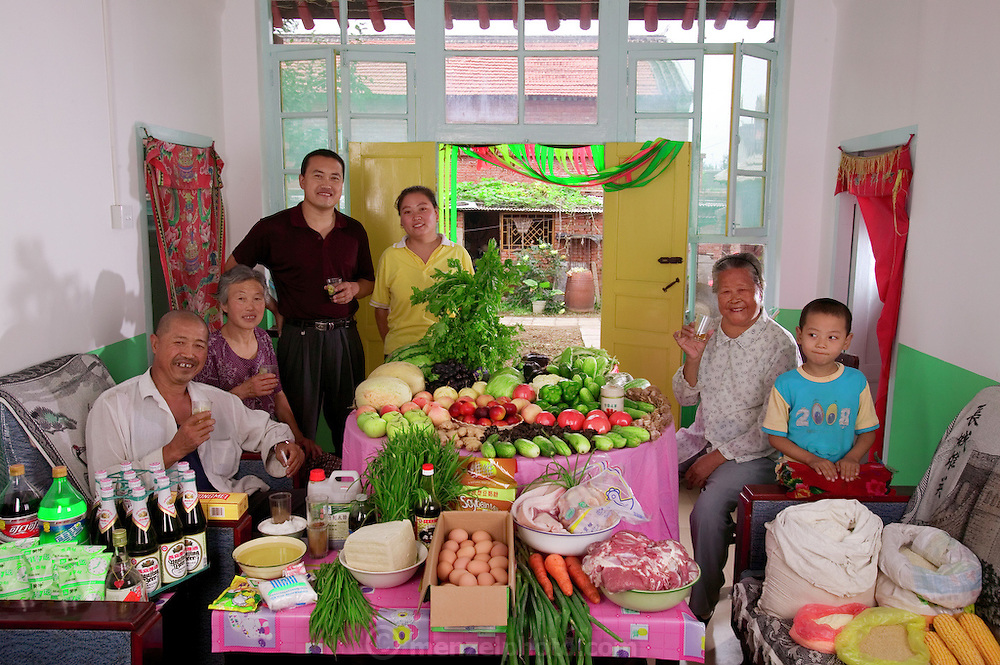 (MODEL RELEASED IMAGE). The Cui family of Weitaiwu village, Beijing Province, in their living room with a week's worth of food. The Cui family is one of the thirty families featured in the book Hungry Planet: What the World Eats (p. 82).