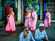"24 NOVEMBER 2017 - YANGON, MYANMAR: Buddhist nuns, also known as ""Bhikkhuni"" pass Muslim men sitting on a Yangon sidewalk. Many Muslims in overwhelmingly Buddhist Myanmar feel their religion is threatened by a series of laws that target non-Buddhists. Under the so called ""Race and Religion Protection Laws,"" people aren't allowed to convert from Buddhism to another religion without permission from authorities, Buddhist women aren't allowed to marry non-Buddhist men without permission from the community and polygamy is outlawed. Pope Francis is to arrive in Myanmar next week and is expected to address the persecution of the Rohingya, a Muslim ethnic minority in western Myanmar. Some Muslims and Christians are concerned that if the Pope's comments take too strong of pro-Rohingya stance, he could exacerbate religious tensions in the country.  PHOTO BY JACK KURTZ"