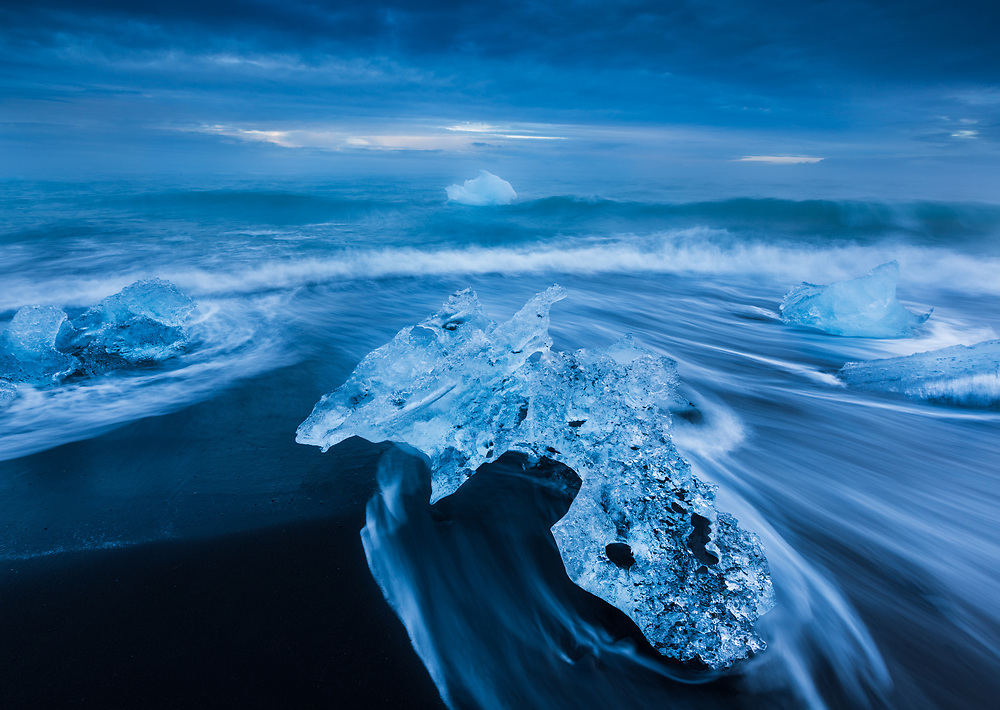 Water pattern caused by receding wave encircles a stranded iceberg along the beach at Jokulsarlon, Iceland