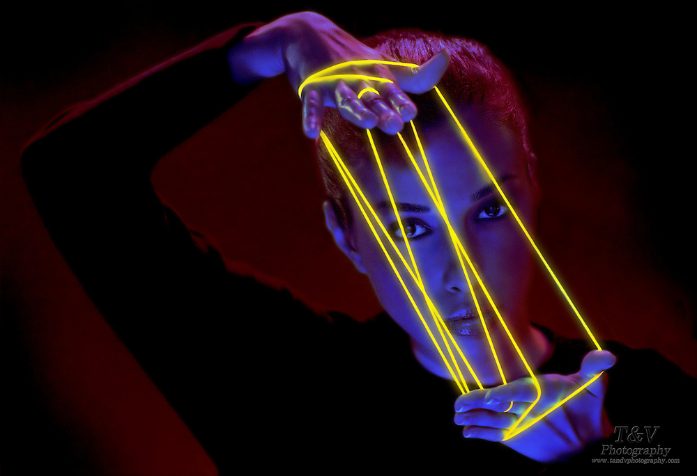 Portrait of a young woman holding glowing yellow string in a cdat's cradle.Black light