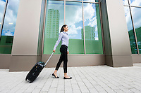 Full length side view of young businesswoman walking with luggage on sidewalk against building