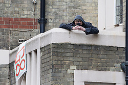 """© Licensed to London News Pictures . 11/06/2013 . London , UK . A man wearing a black face mask on the roof above the entrance where police surround a former police station on 40 Beak Street , Soho this morning (11th June) which has been occupied by organisers as a base for today's """" Stop G8 """" anti capitalist protest . Demonstrations in London today (Tuesday 11th June 2013) ahead of Britain hosting the 39th G8 summit on 17th/18th June at the Lough Erne Resort , County Fermanagh , Northern Ireland , next week . Photo credit : Joel Goodman/LNP"""