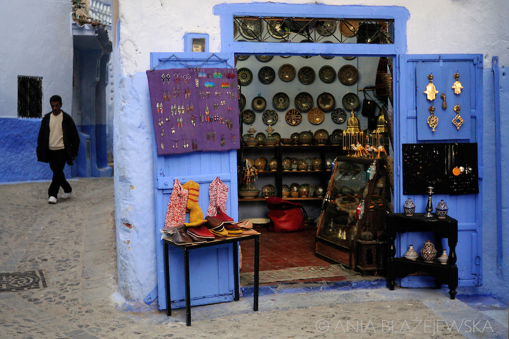 Morocco, Chefchaouen. Man walking near the souvenir shop.