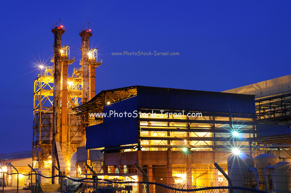 Industrial complex at night on a blue sky background