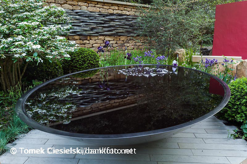 Pool with bubbles and in background stone wall with bicycle wheel rims. Designer: Alistait W. Baldwin