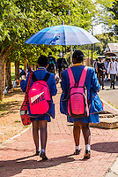 School girls carry umbrellas to shield themselves from the sun, Mkize Street, Rockville, Soweto, Johannesburg, South Africa.