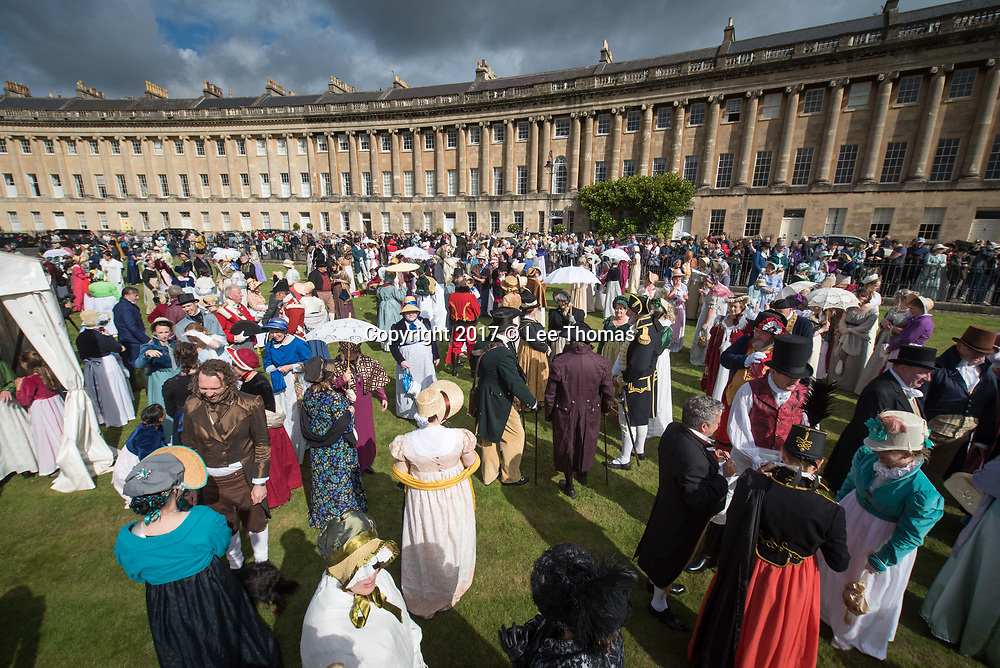 Bath, Somerset, UK. 9th September 2017. Pictured:  Hundreds of costumed participants assemble at Royal Crescent Lawn prior to the Promenade. /  Around 600 people dressed in period attire take part in the Grand Regency Costumed Promenade in Bath marking the 200th anniversary of the English novelist Jane Austen's death. The Promenade commenced mid-morning from the world famous Royal Crescent Lawn and made its way through the historic Georgian streets and main shopping area of the city before finishing at Parade Gardens. In 2014 the Jane Austen Festival achieved the Guinness World Record TM for 'The largest gathering of people dressed in Regency costumes'. The Somerset city is currently host to the 17th annual Jane Austen Festival with an expected 4000 visitors taking part in events such as film screenings, book readings, workshops, dances, balls, talks, concerts and theatricals. // Lee Thomas, Tel. 07784142973. Email: leepthomas@gmail.com  www.leept.co.uk (0000635435)