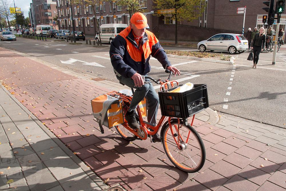 In Apeldoorn fiets een postbesteller van PostNL op een oranje fiets.<br /> <br /> In Apeldoorn a postman of PostNL is cycling on an orange bike.