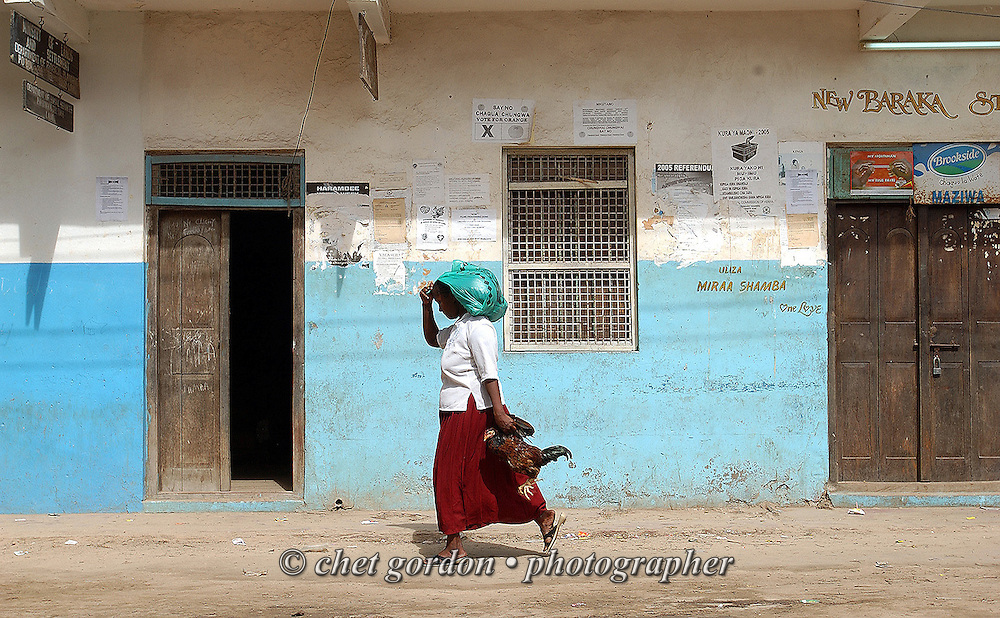 A woman returns from the market with a live chicken in Lamu, Kenya on Sunday, May 14, 2006.
