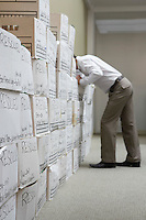 Business man leaning over filing box in storage room side view