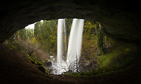 Oregon's North Falls as viewed from within the huge cavern carved out behind the waterfall over many thousands of years. This huge waterfall and a very memorable part of North Silver Creek was formed from 15-16 million-year-old volcanic bedrock (basalt) which has been withstanding the millions of years of water and weather erosion while the surrounding sandstone (once part of the Oregon coastline) which is very slowly wearing away. As it stands now, the waterfall drops 136 and continues downstream through a series of other spectacular waterfalls. The huge cavern behind the falls reaches back about 100 feet, has a ceiling that ranges from 20 to 75 feet high and is (in my estimation) about 800-900 feet wide. Very impressive, to say the least!