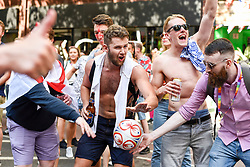 &copy; Licensed to London News Pictures. 07/07/2018. LONDON, UK. England fans in the capital celebrate the England national team's 2-0 victory against Sweden in the quarter-final match of the World Cup in Russia.  Jubilant fans in Charing Cross Road stop passing traffic chanting &quot;Football's Coming Home&quot;.  The annual Pride London event is also taking place in the area with happy rainbow clad Pride participants keen to celebrate as well.  England will face the winner of home team Russia or Croatia in the semi-final.  <br />   Photo credit: Stephen Chung/LNP